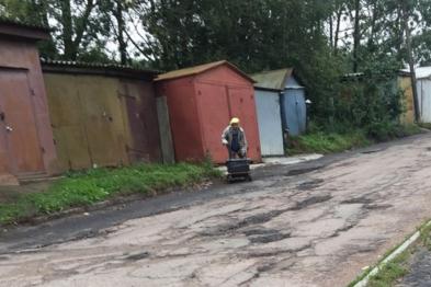 Пожилую женщину, ремонтирующую дорогу вместо сотрудников дорожных служб сфотографировали в Брянске
